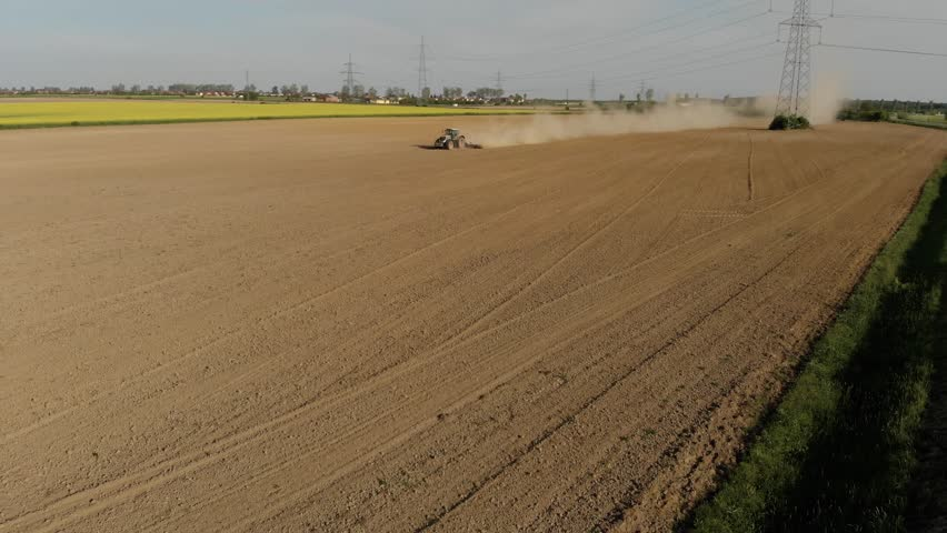 Aerial of tractor on field in dust (top view from height)  | Shutterstock HD Video #1010260412