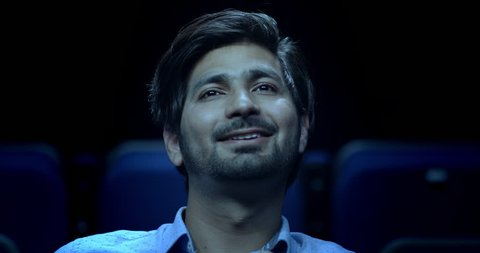 Indian man sat in a dark movie theatre laughing at a funny movie.