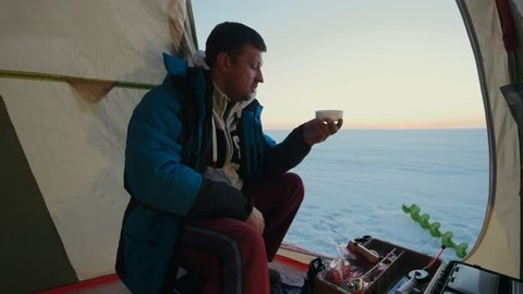Fisherman pouring hot tea in cup from thermos in fishing tent on background morning sunrise in ice lake. Man angler drinking hot tea and using tablet pc winter fishing