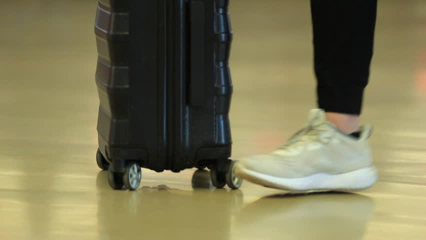 Person carrying luggage at airport. Traveler drags suitcase with wheels | Shutterstock HD Video #1010287502