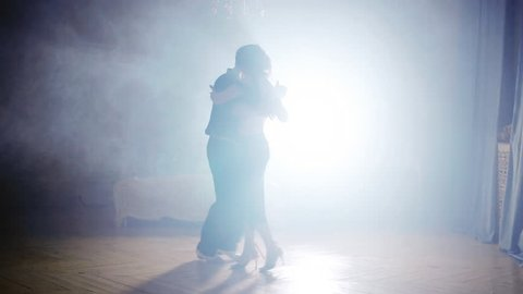 Couple dancing tango in the fog