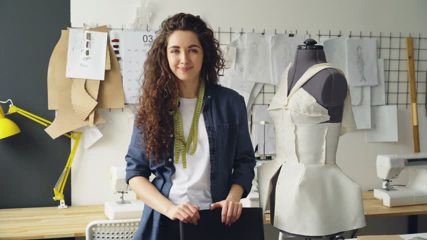 Portrait of beautiful young woman tailor standing in workplace near clothed mannequin and looking at camera. Women's garments, sketches and sewing machines are visible.