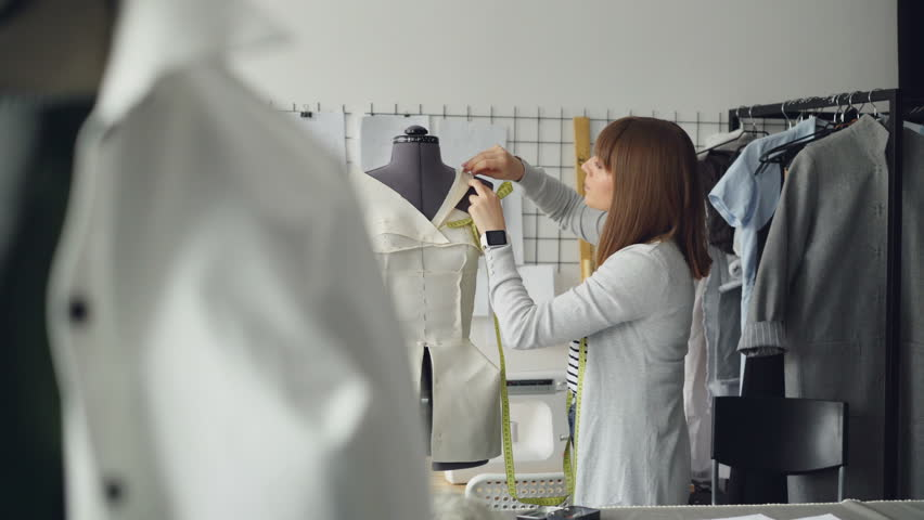 Pretty young woman is adjusting clothes on tailoring dummy with pins while working at new women's clothes in light tailor's shop. Creating new garment concept.
