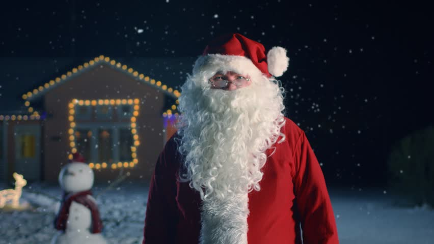 Portrait of Authentic Santa Claus, Waving His Hand. New Year's Eve Santa Brings Joy, Gifts and Presents to Everybody. In the Background House Decorated for Christmas and Falling Snow. 4K UHD.