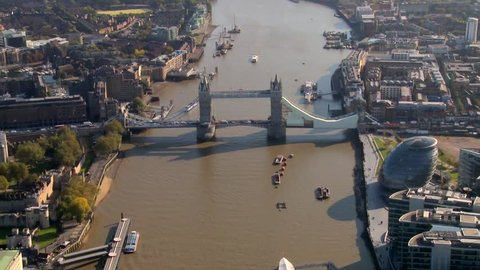 Aerial footage of Tower Bridge, London, England, UK. We circle towards the bridge above the River Thames and can see the Lord Mayor's Office building and the Tower Of London in the shot. HD.
