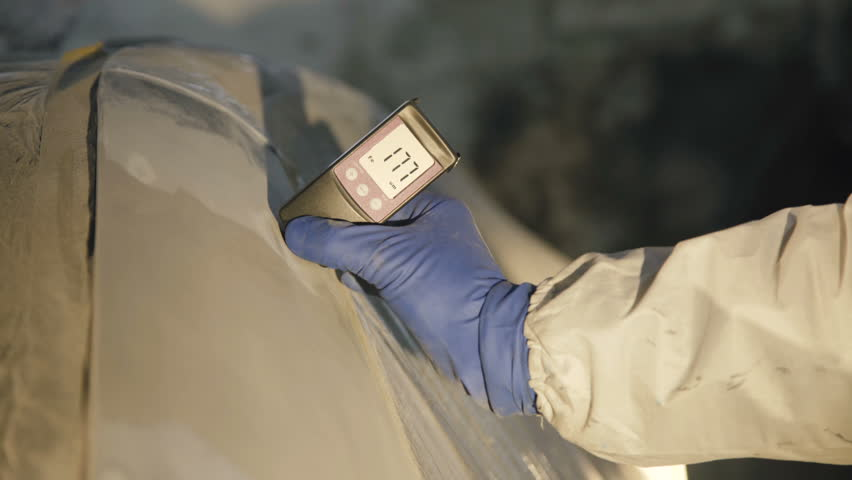 View of measuring a thickness of primer on a car surface using a thickness gauge. 4K