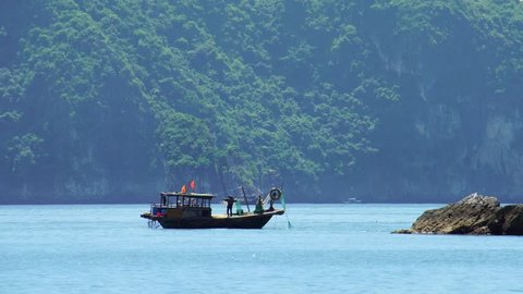 Fishermen rolling fishing nets In Cat Ba Harbor, Halong Bay, Vietnam