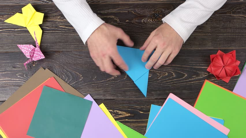 Male Hands Folding Blue Paper Man Making Origami Crane Top View