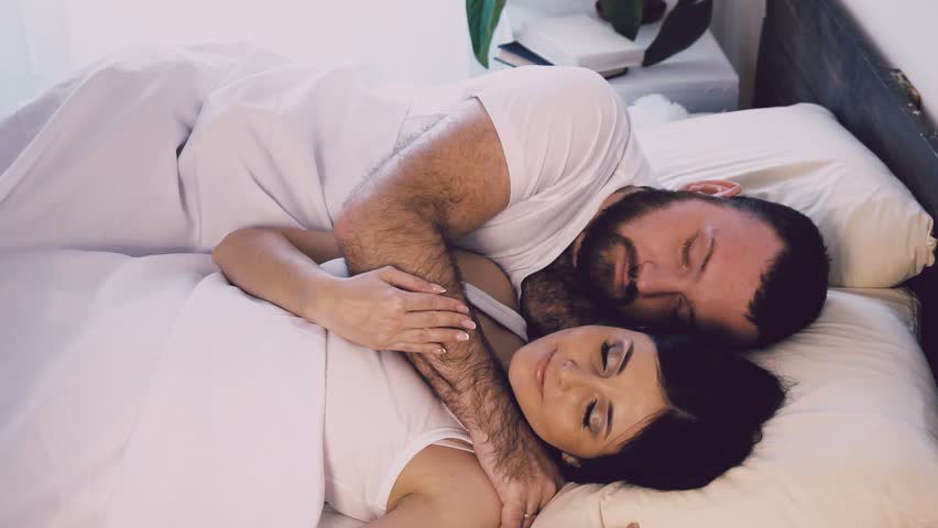 a man and a woman sleeping next to husband and wife