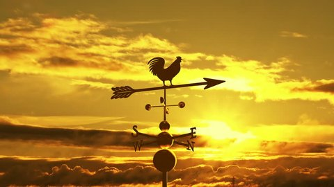 Weathervane cockerel floating against sunset
