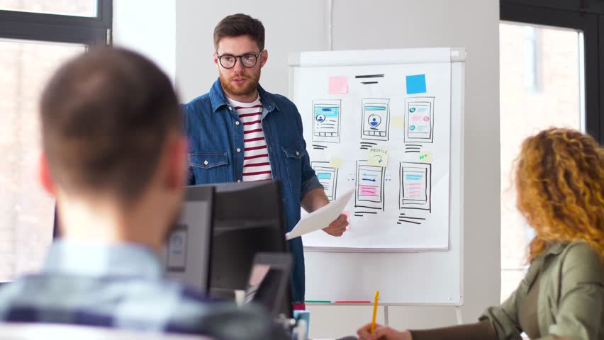 business, technology and people concept - man showing user interface design on flip chart to creative team at office presentation