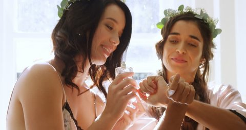 Happy bridesmaids in nightdress and head wreath are smelling and applying perfume at home 4K 4k
