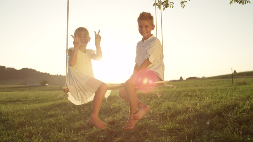 SLOW MOTION PORTRAIT: Couple smiling kids playfully pose for camera. Little brother and sister sitting on wood swing smile and pose at sunset. Cheerful siblings enjoy a warm summer evening on a swing