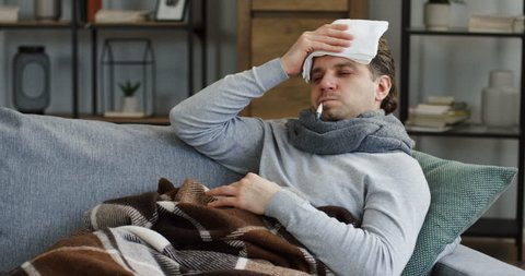 Unhealthy caucasian man covered with a plaid sitting on the gray sofa at home, checking his temperature with a thermometer as he having an influenza and fever, holding a towel on the forehead. Indoors