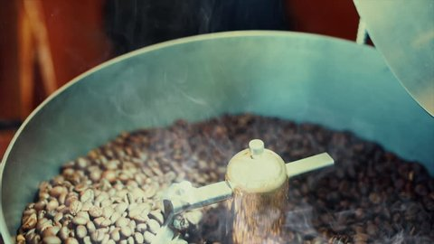 Mixing of roasted coffee. Partial removal of bad grains. The roasted coffee beans got on the mixer sorting by a professional machine. Slow motion.