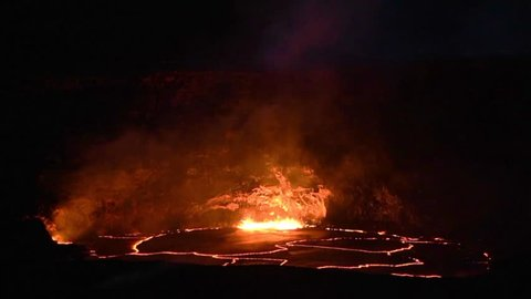 Hot molten lava bubbles and lights up Halemaumau crater at night - taken from the rim of the Kilauea caldera in Hawaii Volcanoes National Park on the Big Island