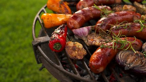 Grilled sausages and vegetables on a grilled plate, outdoor. Grilled food, bbq, 4K