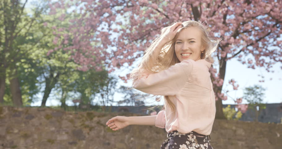 The young attractive girl with long blonde hair is turning round and running along the beautiful blooming sakura garden. 4k footage.
