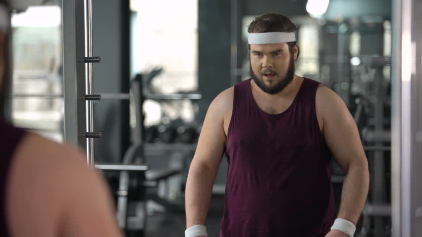 Funny fat man looking at mirror reflection gym and posing, pretending muscular | Shutterstock HD Video #1010521682
