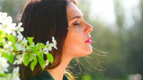 Beauty young woman enjoying nature in spring apple orchard, Happy Beautiful girl in Garden with blooming trees. Aroma. Smiling Female smelling blossom flowers 4K UHD slow motion video 3840X2160