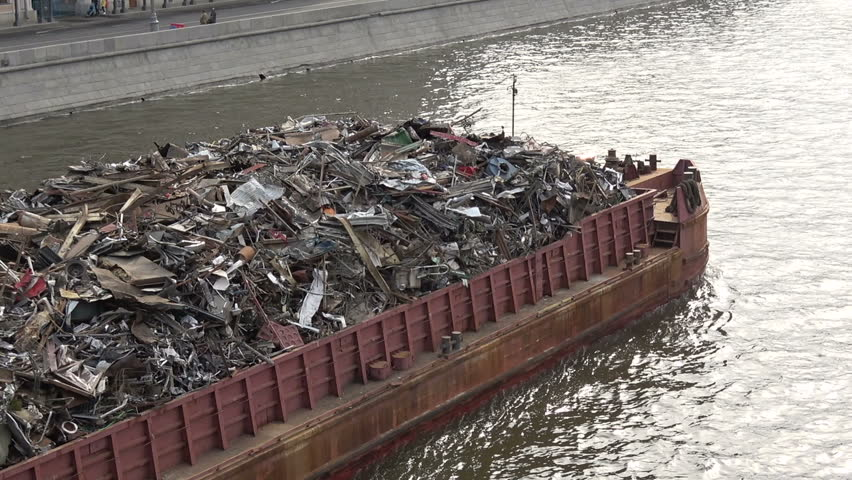Barge laden with metal scrap swims along the river