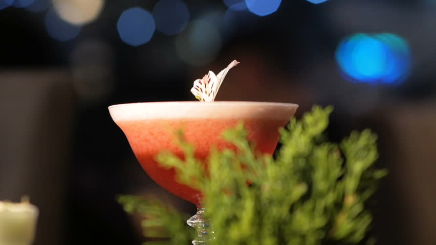 Closeup of bartender pouring drink into the glass with beautifully preapred decoration.Barman mixing exotic drink | Shutterstock HD Video #1010556272