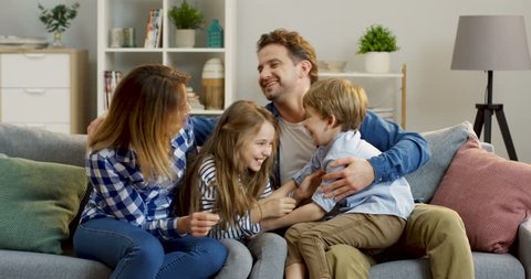 Nice Caucasian family: mother, father and their children, having fun on the sofa in the living room, tickling and laughing. Indoor