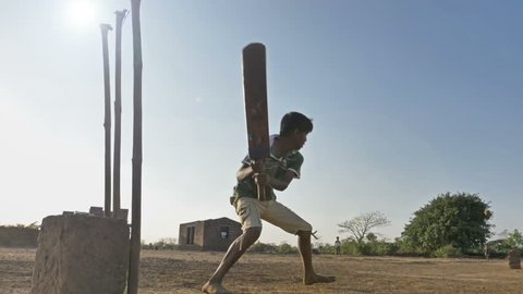 Slow motion shot of a young kid hits the ball and runs in village. Outdoor shot of  Group of children playing cricket in a open field.