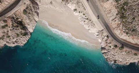Descending aerial drone video top down bird's eye view of turquoise Mediterranean water, waves breaking on Kaputas Beach near Kas, Turkey. 4k at 23.97fps