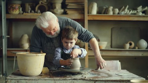 Concentrated young boy is molding clay into ceramic vase on spinning throwing wheel and his experienced grandfather is helping him. Pottery and family tradition concept.