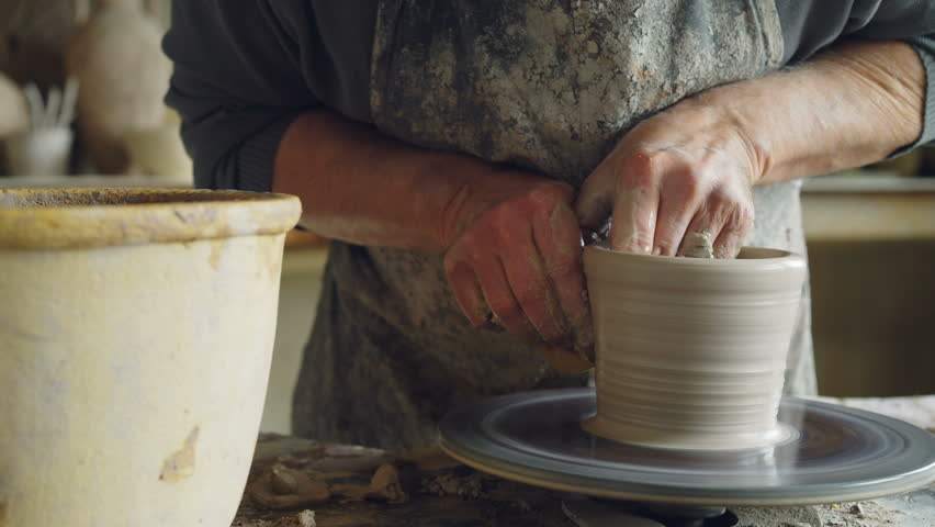 Close-up shot of half-finished ceramic vase spinning on potters's wheel and hands molding clay with professional tools. Creating eathenware and traditional pottery concept.
