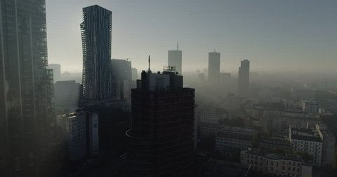 Drone footage of skyscrapers and buildings in Warsaw city center. Shot is taken during a misty but sunny day in Poland.