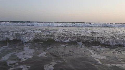 Man running in beach water at evening time. Beautiful Mandvi Beach, Gujarat, India.