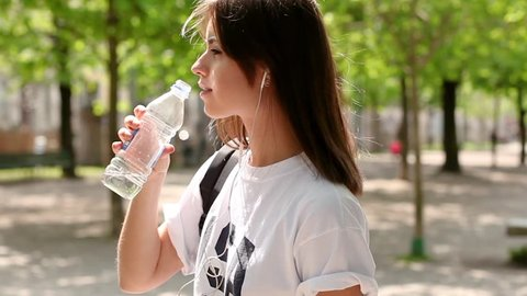 Brunette teenager girl drinking cold water after running in the park in the fresh air during sunny day, beautiful fitness athlete woman drinking water after work out, health and sport, flare light