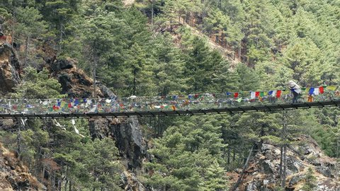 Largest suspension bridge in Solu Khumbu valley with colorful prayer flags, trekking area to the base camp of Everest peak (8848 m).
