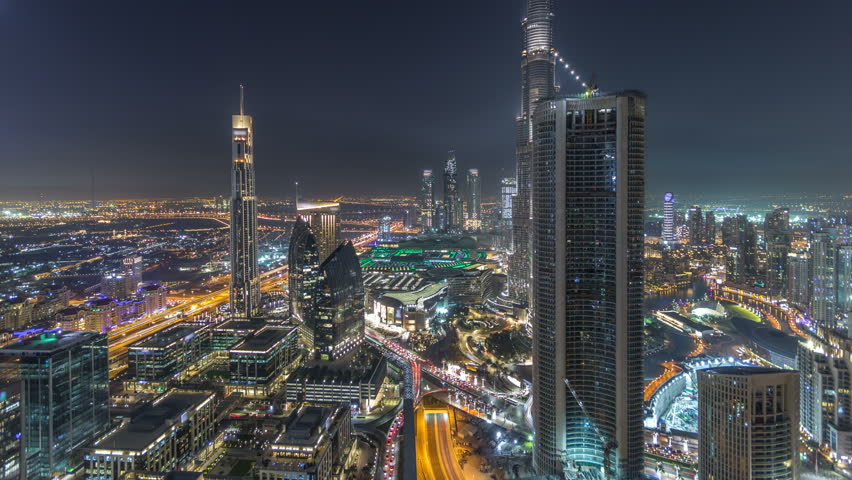 Dubai Downtown night timelapse modern towers panoramic view from the top in Dubai, United Arab Emirates. Traffic on the road and music fountain