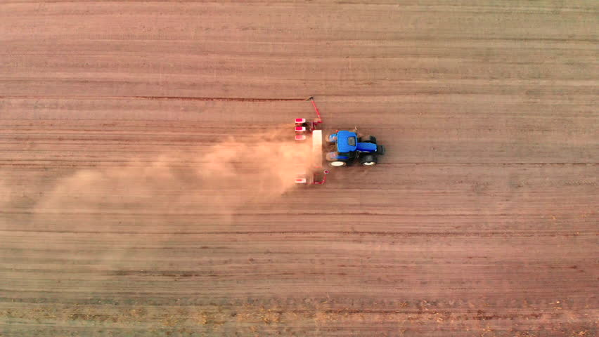 4K Aerial footage of a modern tractor plowing dry field.