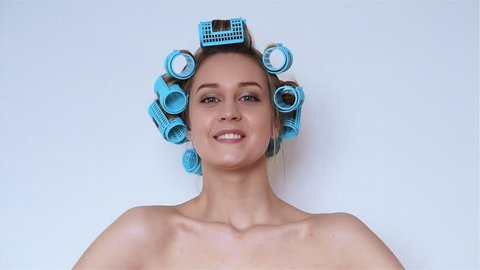 Smiling girl in hair curlers isolated