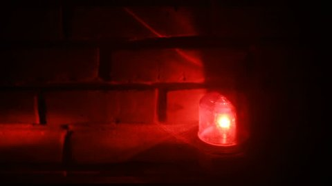 closeup view of bright red flashlight moving around in dark space and brick orange wall on background inside nobody lamp light emergency lights police lights siren signal traffic flare ambulance sign