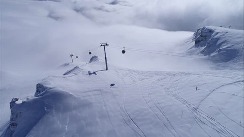 Aerial view over snowy mountain ridge valley with clouds, cable car lifting. Gondola transportation on the cliff in winter. High altitude gondola in winter. Ski Gondola. Above the clouds gondola ski