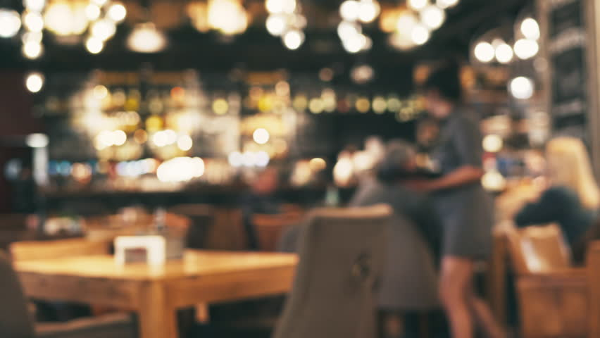 Blurred picture of the interior of a large beautiful restaurant with bright lighting. The waitress comes to the table and gives the visitors a menu and goes for drinks. Defocused restaurant | Shutterstock HD Video #1010750342