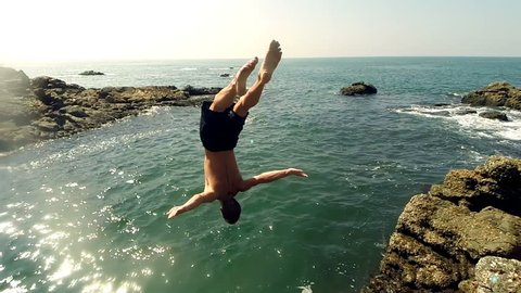 Male athlete jumping from a cliff into the water. Athletic young man doing back flips into sea. Slow-motion.