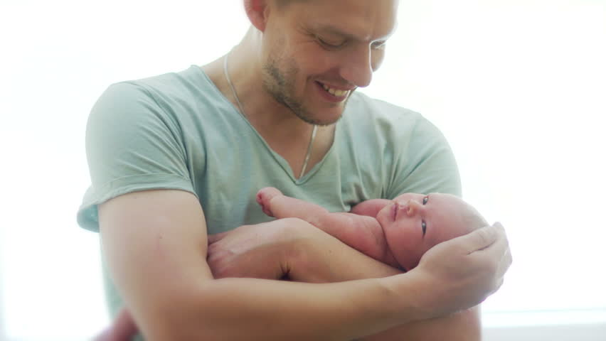 A young father of athletic builds a naked newborn baby on his hands. A man strokes him on the head, the child waves with a pen and turns his head, looks around. Father's Day
