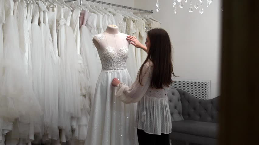 Beautiful girl looking wedding dress in the cabin compared to other dresses. Preparing for the wedding. Buying a wedding dress. The seamstress inspects the finished custom made wedding dress. | Shutterstock HD Video #1010765552