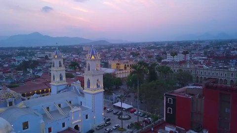beautiful aerial panoramic travel of the Cathedral of the Sanctuary of the Immaculate Conception in the center of Cordoba, Veracruz with a beautiful sunset in the background