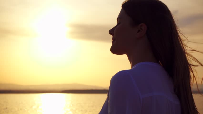 Dark silhouette of smiling young woman at sunset on lake. View from the side, close up of carefree female figure at golden hour in slow motion #1010811902