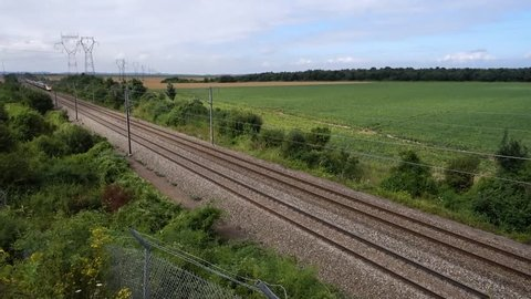High angle view of Passing French highspeed train in rural summer natural landscape, High-voltage direct current on the background