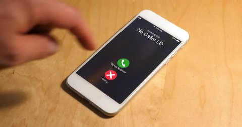 A cellular telephone on a desk rings with a phone call from a caller with no caller ID. The call is ignored. Phone number and screen are fictional.