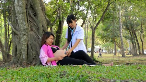 Asian woman doctor is checking pregnant girl in a state of emergency in a pubic park.
