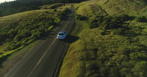 Aerial view of car driving down country road through rural rolling hills at sunset